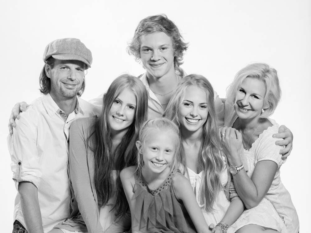 Mamma och pappa med sina fyra barn i en rolig svartvit familjefotografering