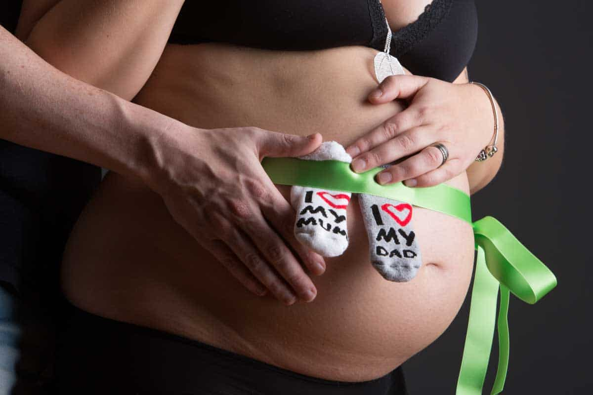 Gravidfotografering med barnsmycken. strumpor eller skor